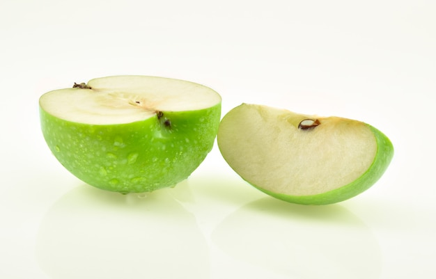 Green apple with drop of water on white.