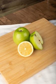木の板に新鮮なレモンと青リンゴ。上面図