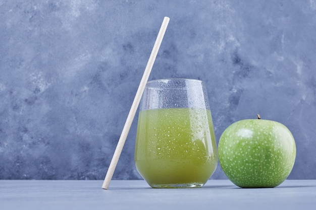 A green apple with a glass of juice.