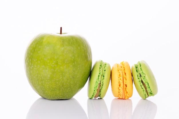 Зеленое яблоко с зеленым и желтым миндальным печеньем