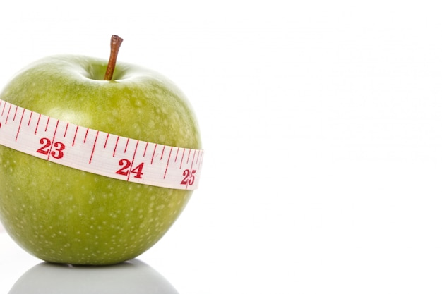 Green apple with measurement tape. healthy concept.
