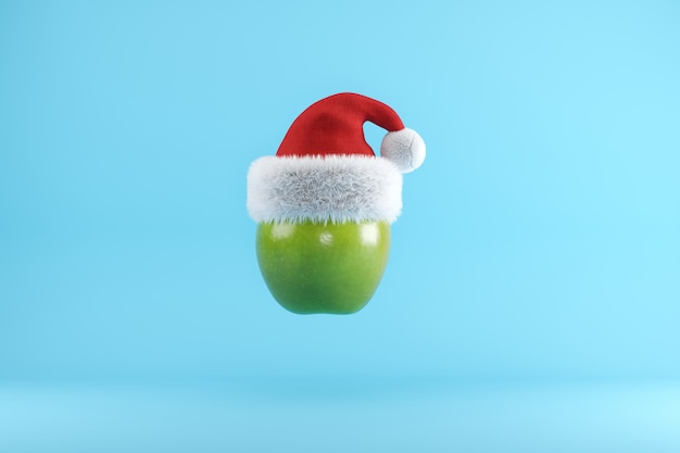 Green apple with santa hat floating on blue