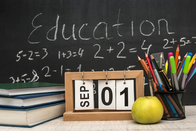 Green apple with stack of books and writing supplies against blackboard. education concept