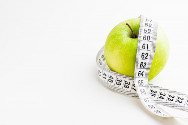 Green apple with tape measure on white desk. health and diet.