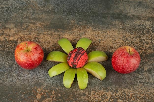 Mela verde con due mele fresche rosse sulla superficie di marmo.