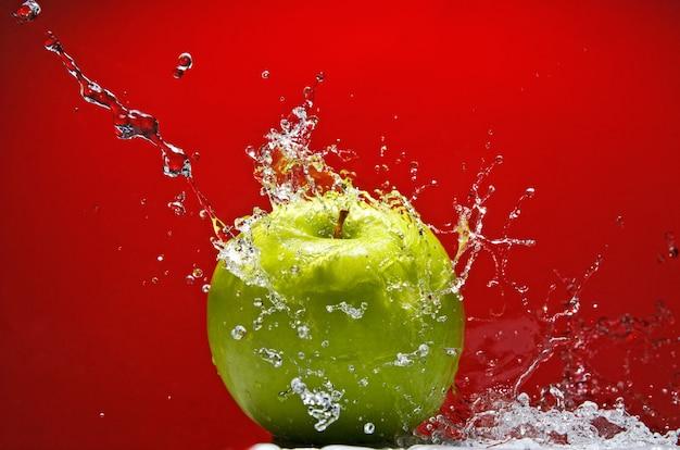 Зеленое яблоко с брызгами воды на красной стене