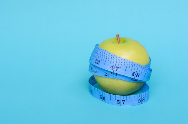 Green apple wrap by measuring tape to measure length on a green background