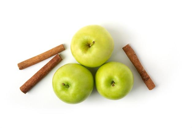緑のリンゴと白で隔離される桂皮