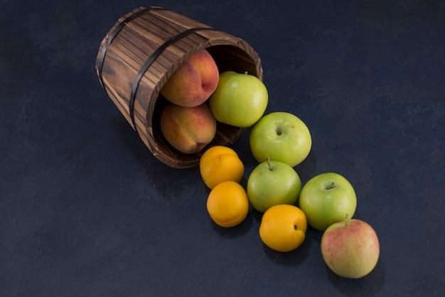 중앙에있는 나무 통에서 녹색 사과 오렌지.