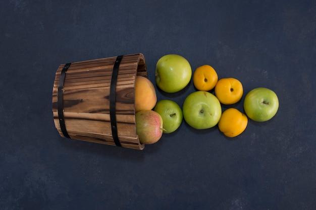 真ん中の木製のバケツから青リンゴとオレンジ。