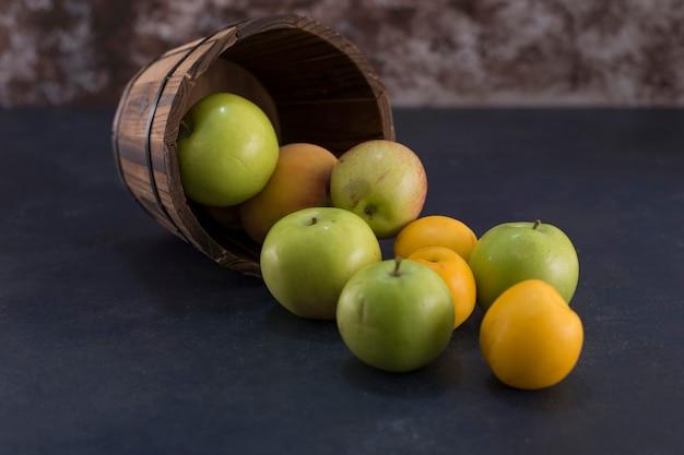 緑のリンゴとオレンジの木製バケツ