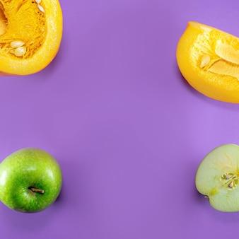 Зеленые яблоки и тыква на фиолетовом фоне