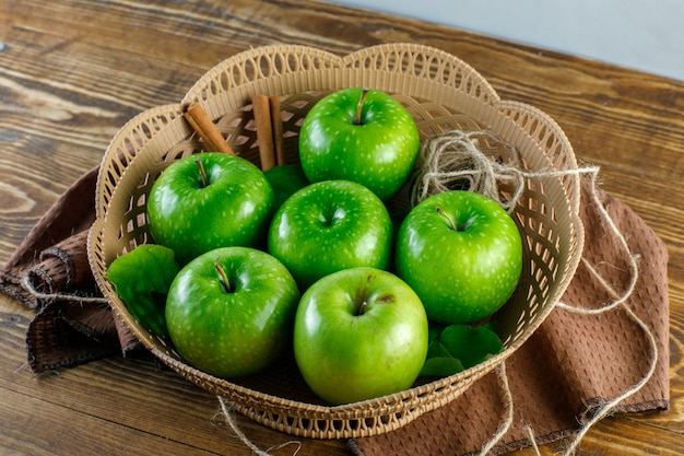 Green apples in a basket with cinnamon sticks, rope, kitchen  towel, leaves high angle view on wooden table