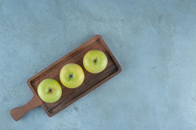 Mele verdi su una tavola, sullo sfondo di marmo. foto di alta qualità