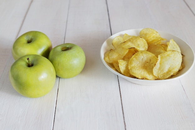 Green apples and a bowl of potato chips
