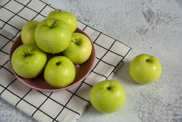 Green apples in a ceramic saucer on the table
