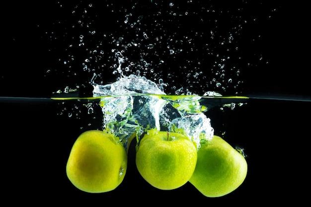 黒に対してスプラッシュで水に落ちる青リンゴ