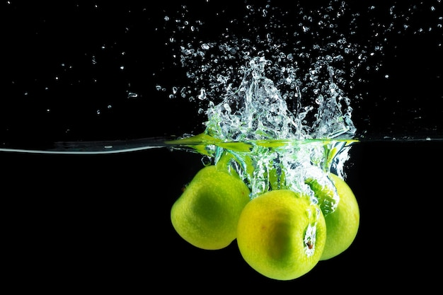 Green apples falling into the water with a splash against black