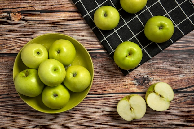 Green apples in a green ceramic bowl on a checked towel