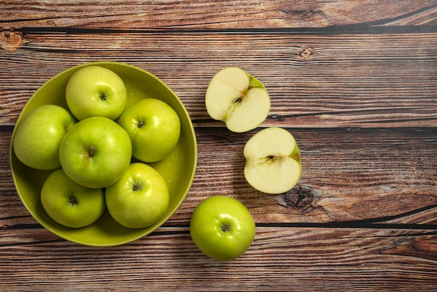 Green apples in a green ceramic bowl, top view