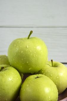 Зеленые яблоки в керамическом блюдце