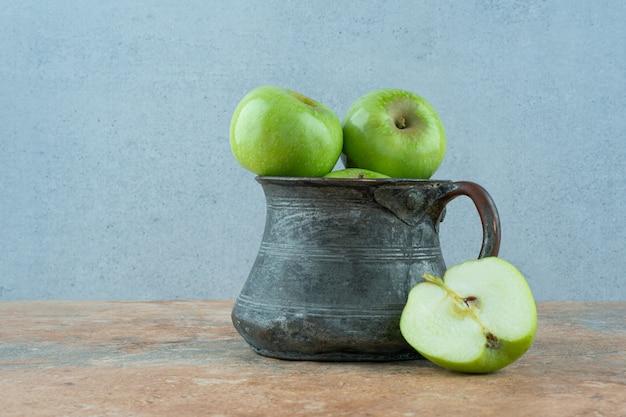 Зеленые яблоки в железной посуде.