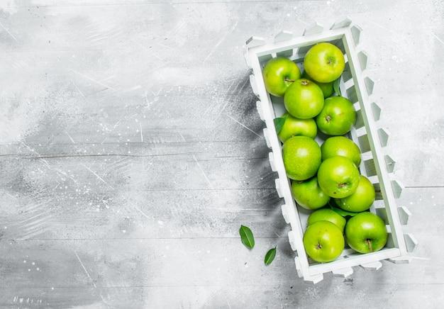 プラスチックの箱に入った青リンゴ。白い素朴な背景に。