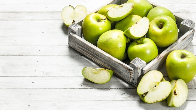 작은 상자에 녹색 사과. 흰색 나무 바탕에.