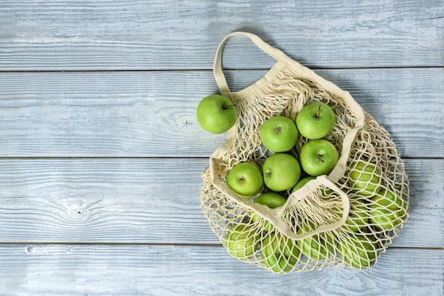 木製のテーブルの上のストリングバッグの青リンゴ。コピースペースのあるフラットレイコンポジション。