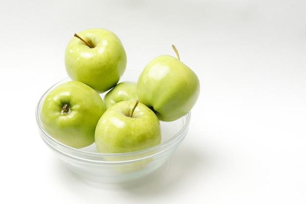Зеленые яблоки в прозрачной миске на белом фоне