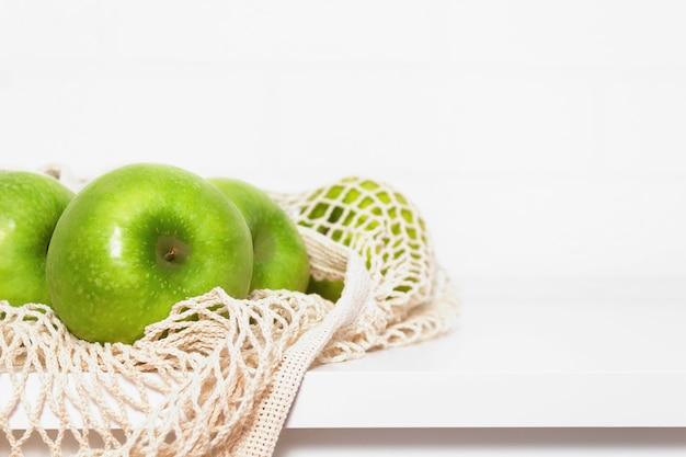 白い台所のテーブルの上のエコメッシュバッグの青リンゴ。マーケットショッピング。
