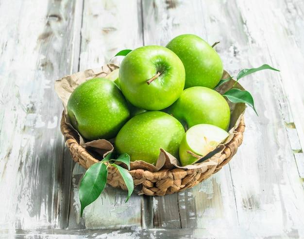 かごの中の青リンゴ。白い木製のテーブルの上。