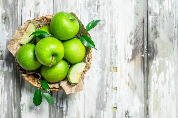 白い素朴なテーブルのバスケットに青リンゴ。