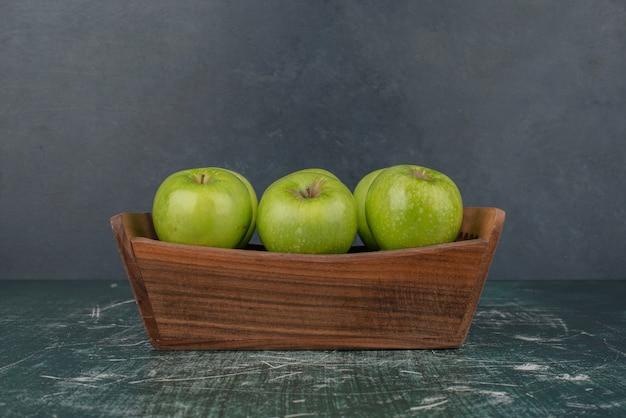 Зеленые яблоки в деревянном ящике на мраморной поверхности.