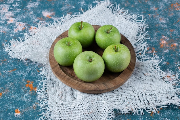 Green apples isolated on wooden board.