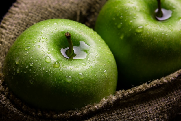 Green apples in a jute bag with water drops on a dark wall