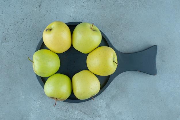 大理石の背景に、鍋に青リンゴ。高品質の写真