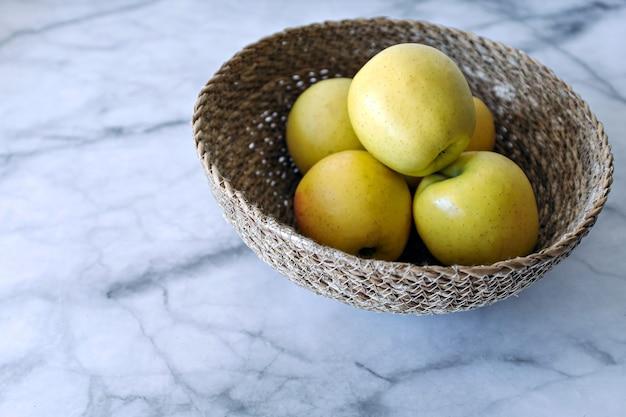 白い大理石のテーブルの上の青リンゴ
