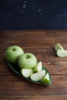 木製のテーブルの上の青リンゴ。閉じる。健康食品の概念。まな板の上でスライスした青リンゴ
