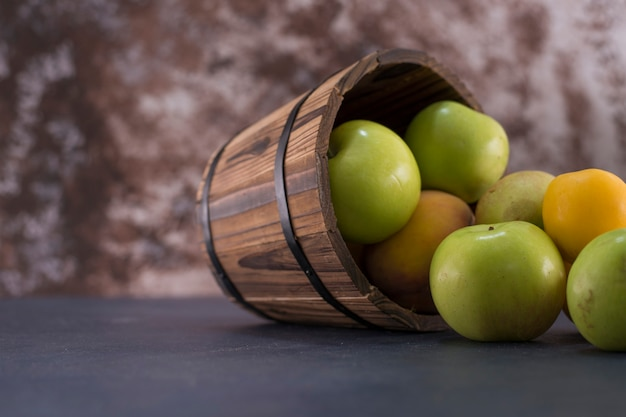 Green apples and oranges out of a wooden bucket.