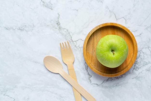 Зеленые яблоки положить в деревянную миску рядом с деревянной ложкой и вилкой