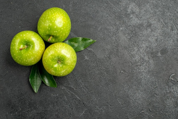 Green apples three green apples with leaves on the dark table