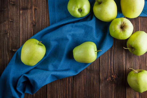 Vista superiore delle mele verdi su un panno blu e su un fondo di legno