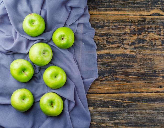 Vista superiore delle mele verdi sul fondo del tessuto e di legno