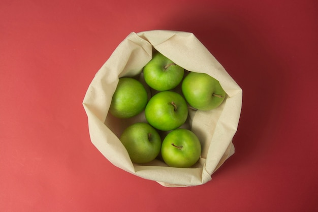 Green apples in  tote bag over red background . zero waste concept.