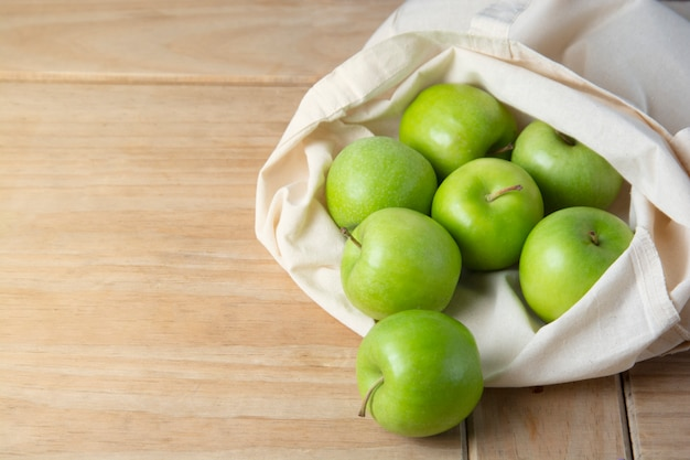 Green apples in  tote bag over wooden background . zero waste concept.