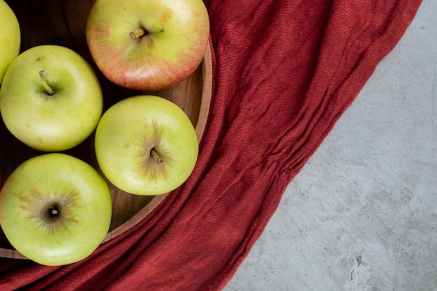Green apples on a tray on marble surface