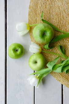 Green apples and tulips on a straw hat and on the background of wooden boards