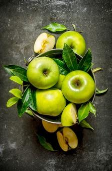Зеленые яблоки с листьями в ведре. на деревенском каменном фоне. вид сверху