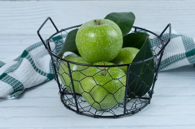 Зеленые яблоки с листьями в металлической черной корзине на белой поверхности. .